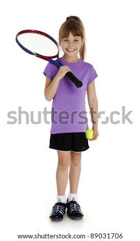 Full length studio photo of seven year old girl holding tennis racket and tennis ball isolated on white.