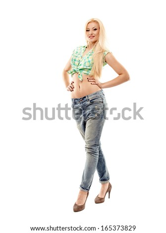 Full length studio portrait of sexy blonde wearing jeans and shirt standing akimbo isolated over white background - stock photo