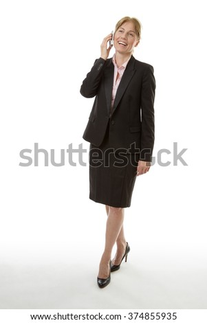 Full length studio shot of a mature businesswoman walking talking on mobile phone, isolated on white background. - stock photo