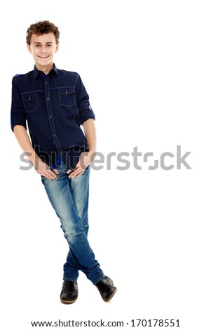 Full length studio shot of a trendy handsome teenager with hands in pockets, isolated over white background, leaning against the side of the image - stock photo