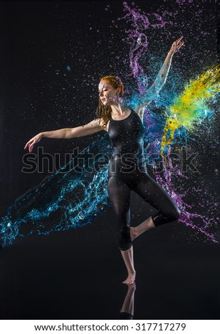 Full Length Studio Shot of Elegant Young Dancer Being Splashed with Colorful Water - Young Red Haired Woman in Ballet Pose in Black Studio - stock photo