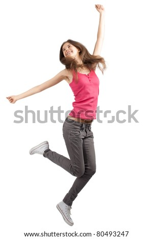 Full length studio shot of happy young woman jumping with arms extended . Over white background - stock photo