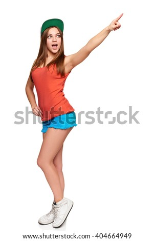 Full length surprised girl pointing at blank copy space, over white background - stock photo
