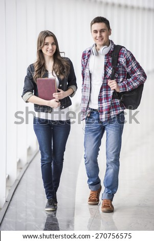 Full length. Two young atractive studens in college. - stock photo