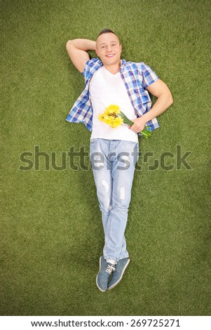 Full length vertical shot of a relaxed young guy lying on grass in a meadow, holding a bunch of yellow tulips and looking at the camera - stock photo