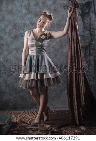 full length vertical studio image of a model standing next to brown drapery wearing a short gray and green handmade layer dress with embroidered floral pattern on a gray background - stock photo