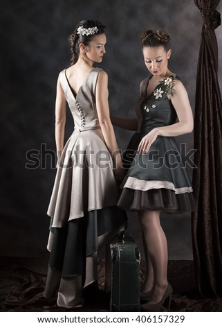 full length vertical studio image of two female models posing wearing layered green and gray dresses standing with a suitcase next to velvet drapery and a gray background - stock photo