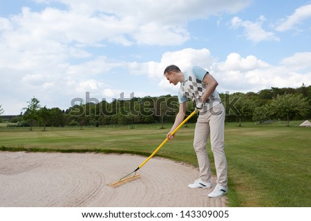 full length view of a golfer racking sand - stock photo