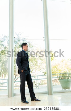 Full length view of a handsome businessman pacing inside a tall building and waiting for a job interview - stock photo