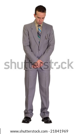 Full length view of a man bowing his head to pray, isolated against a white background - stock photo