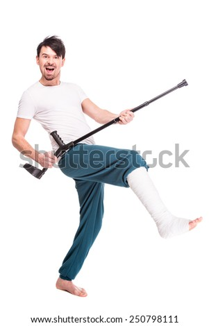 Full length view of a smiling man with broken leg is using crutch and dancing isolated on white background. - stock photo