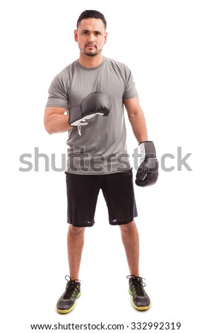 Full length view of a strong boxer with gloves showing his muscles before a fight - stock photo