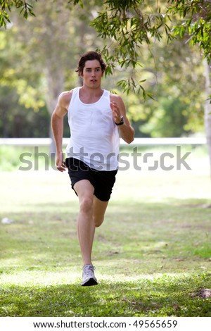 Full length view of a young man jogging in an outdoor setting. He is wearing a tank top and shorts. Vertical shot. - stock photo