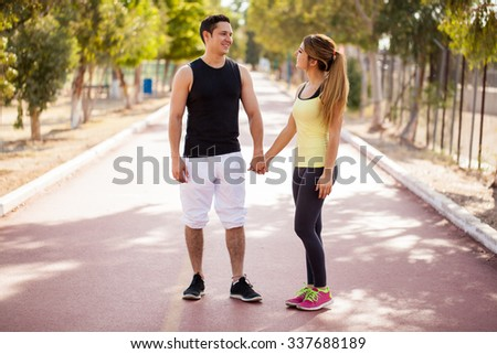 Full length view of an attractive young couple holding hands at a running track outdoors - stock photo