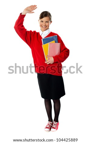 Full length view of cheerful school girl holding exercise books