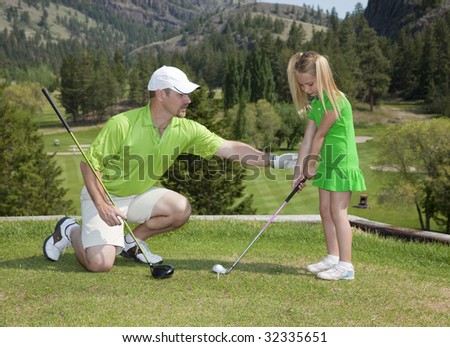 Full length view of father and giving young daughter golf lesson. - stock photo