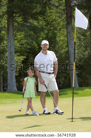 Full length view of father and young daughter standing on golf green. - stock photo