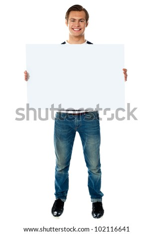 Full length view of happy smiling young man showing blank signboard - stock photo