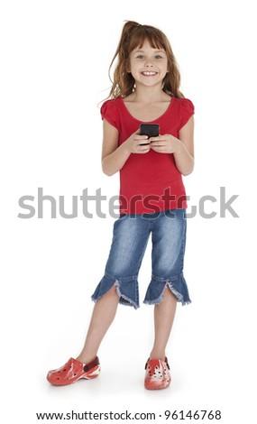 Full length view of little girl standing, holding smart phone, on white background. - stock photo