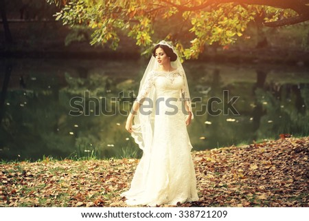 Full length view of one beautiful sensual young brunette bride in long white wedding dress and veil standing near river in autumn leaves outdoor on natural background, horizontal picture - stock photo