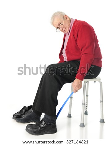 Full length view of senior adult looking at the viewer as he puts his loafers on with a long-handled shoe horn.  On a white background. - stock photo