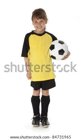 Full length view of seven year old girl holding soccer ball on white background - stock photo