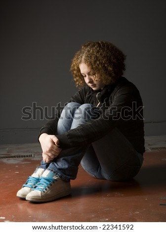 Full length view of teenage girl seated on floor looking depressed. - stock photo