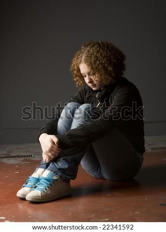 Full length view of teenage girl seated on floor looking depressed. - stock photo
