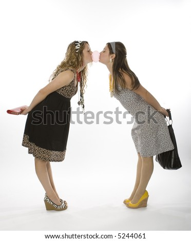 Full length view of two fashionable teenage girls blowing bubblegum.