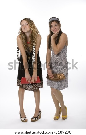 Full length view of two fashionable teenage girls posing.