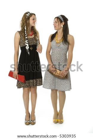 Full length view of two fashionable teenage girls posing silly.