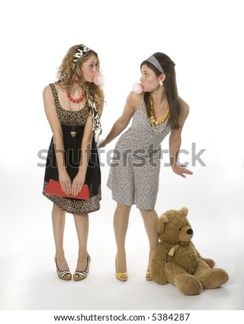 Full length view of two teenage girls blowing bubble gum. - stock photo