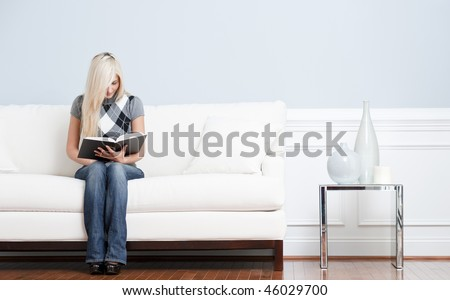 Full length view of woman sitting on a white couch with a book. Horizontal format. - stock photo