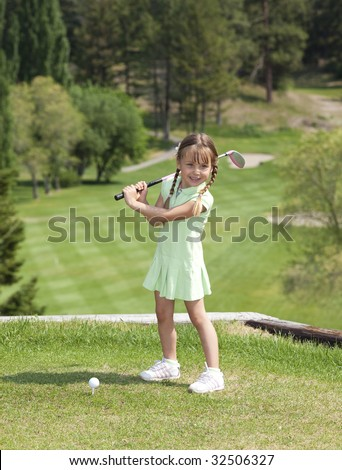 Full length view of 5 year old girl swinging golf club. - stock photo