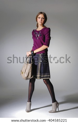 Full length Vogue style fresh beautiful fashion model holding bag over light