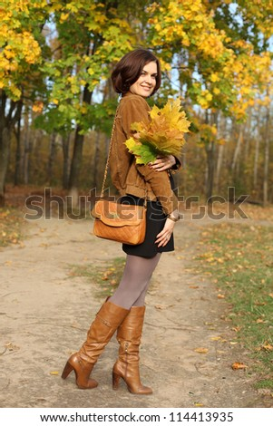 Full length, walking woman in autumn park - stock photo