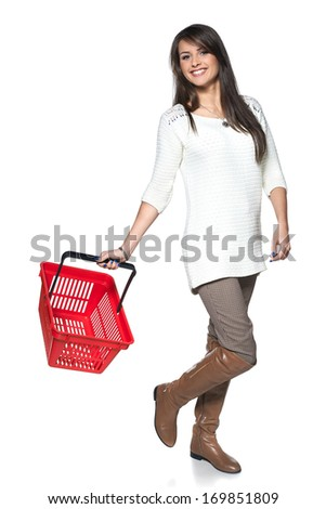 Full length woman walking with red shopping basket, white background - stock photo