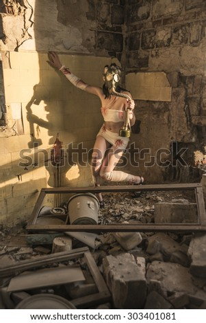 Full length Woman with gas mask in a grunge background Post apocalypse girl stand in angle abandoned dirty yellow wall with shadow from sun light Toxic trash in dusk room Window fram lie on floor - stock photo