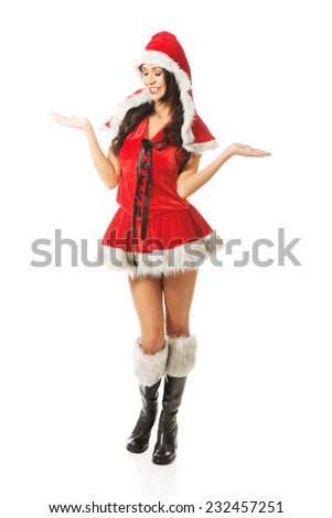 Full length woman with open hands gesture wearing santa clothes. - stock photo