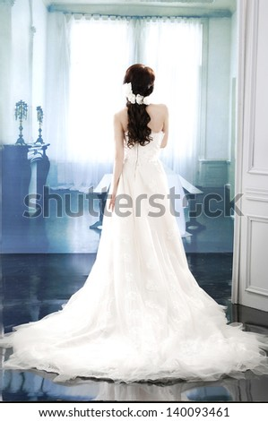 full-length young and beautiful bridge in white dress back in studio - stock photo