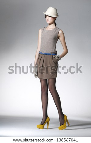 Full length young fashion model in hat walking - stock photo