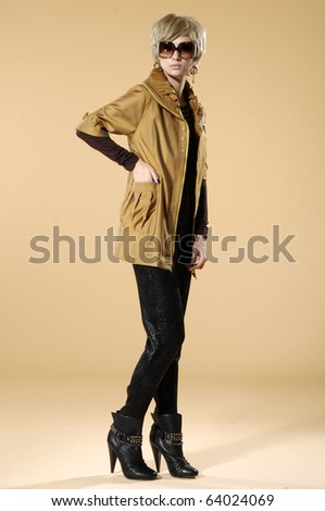 Full length young fashion model posing wearing sunglasses- beige background