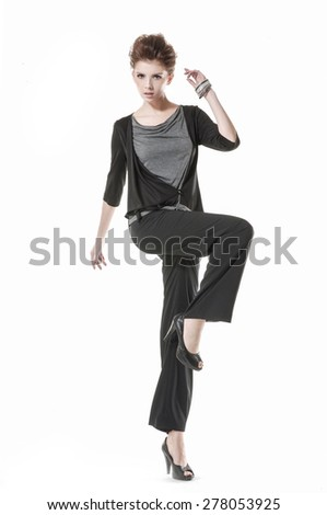 full-length young girl wearing black dress standing in studio