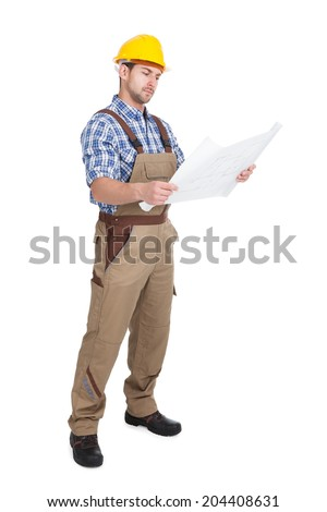 Full length young male worker reading blueprint over white background - stock photo