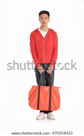 Full length young man in jeans holding handbag standing in studio