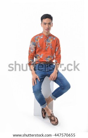 Full length young man in jeans sitting cube in studio - stock photo