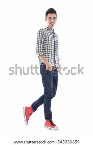 Full length young man in jeans standing with hands in pockets walking in studio