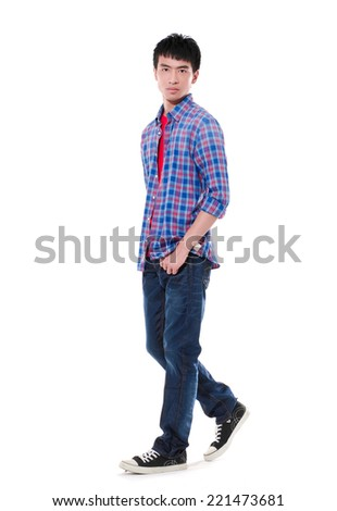 Full length young man in jeans with hands in pockets walking in studio