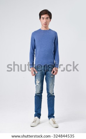 Full length young man standing in jeans posing in studio - stock photo