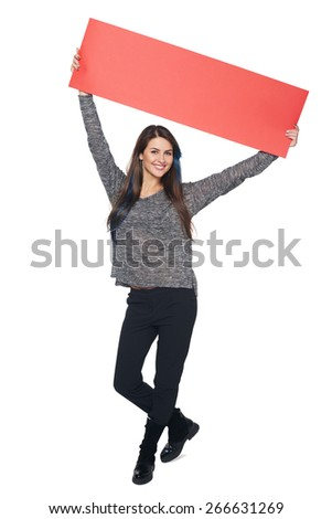 Full length young woman holding red blank cardboard over head, over white background - stock photo